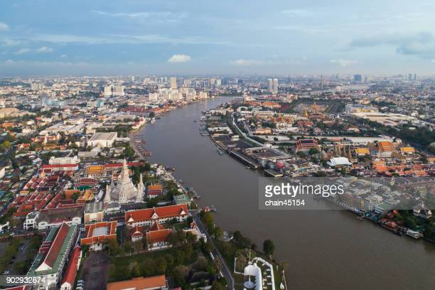 Aerial view of Bangkok Thailand city with Royal grand palace / Wat Phra Kaew / Wat Arun Temple / Chaophraya river with blue sky and boat transportation. All is most popuplar destination travel in Bangkok center city of Thailand.