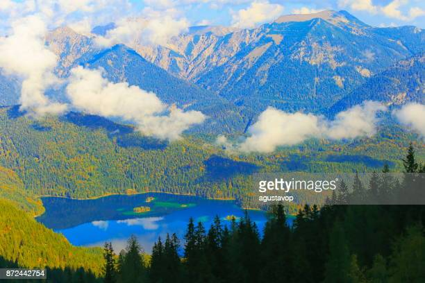 Aerial view of Beautiful and idyllic Eibsee alpine turquoise lake with reflection at gold colored sunrise, view from above Zugspitze mountain peak – dramatic and majestic landscape in Bavarian alps, gold colored autumn  – Garmisch, Bavaria, Germany