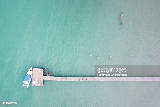 aerial view of beautiful beach with wooden pier and sailing boats background. - surat thani province stock pictures, royalty-free photos & images