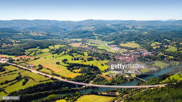 aerial view of beautiful french countryside with elevated highway small village and beginning of alps mountains in background - auvergne rhône alpes stock pictures, royalty-free photos & images