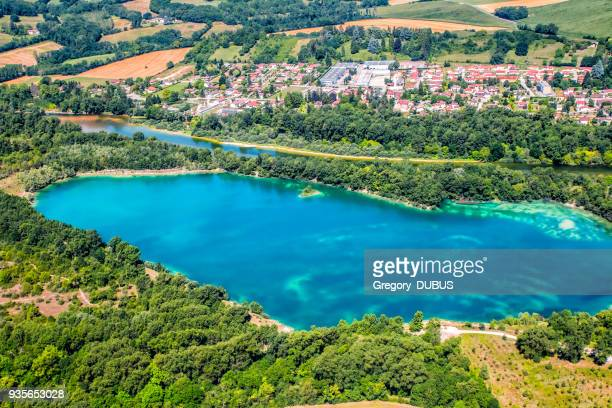 aerial view of beautiful lake with ain river in background in france with town in lush foliage countryside in summer - rhone alpes stock photos and pictures