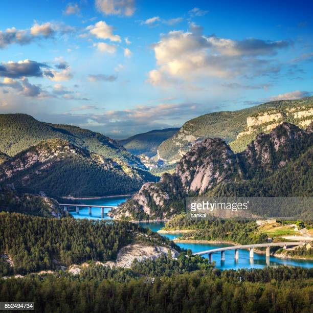 Aerial view of beautiful turquoise lake in mountains and bridges across it.