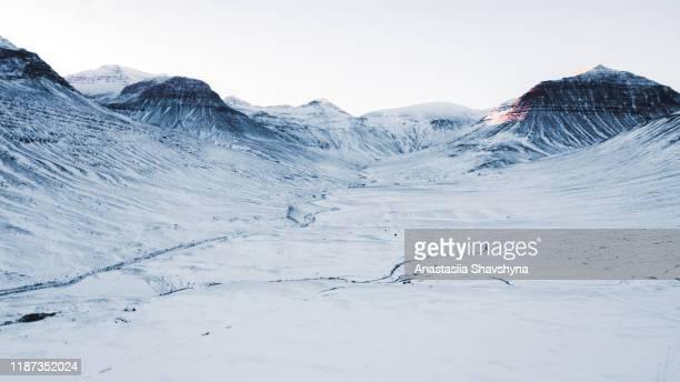 vista aerea della bellissima strada invernale e delle montagne durante il tramonto nel nord dell'islanda - clima polare foto e immagini stock