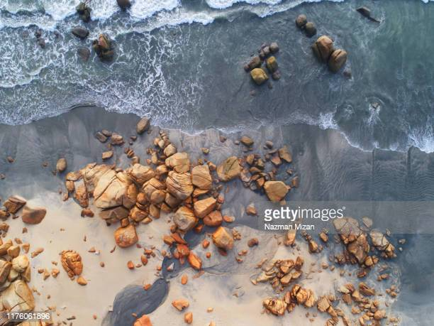 aerial view of big boulders at the beach. - rock stock pictures, royalty-free photos & images