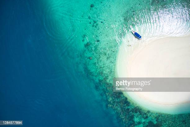 aerial view of boat floating on beautiful coral reef in crystal clear water, phuket, thailand. - clear sky stock pictures, royalty-free photos & images