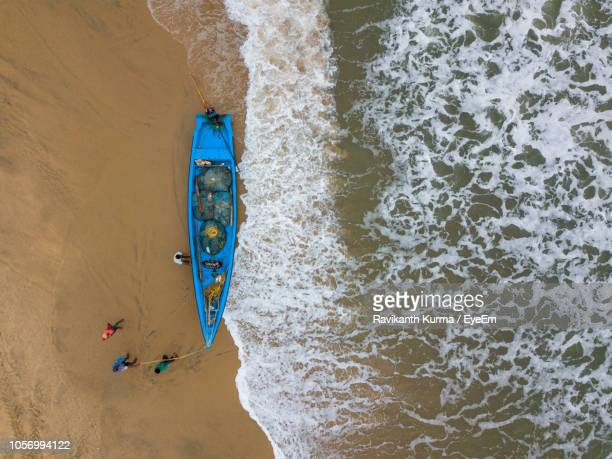 aerial view of boat moored at beach - beauty in nature stock pictures, royalty-free photos & images