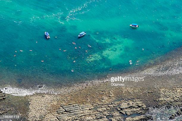 Aerial view of boats and people snorkeling