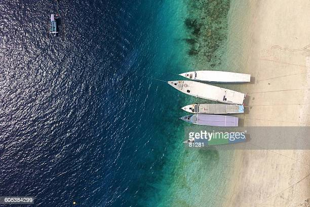 aerial view of boats on beach, gili trawangan, lombok, indonesia - gili trawangan stock photos and pictures