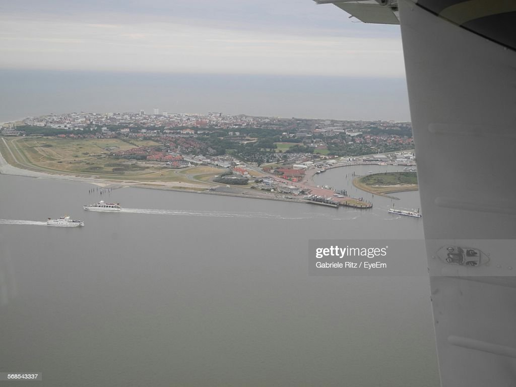 Aerial View Of Boats Sailing On Sea By Cityscape Seen From Airplane Window : Stock Photo