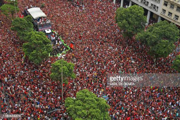 TOPSHOT Aerial view of Brazil's Flamengo fans surrounding a bus carrying the Flamengo football team during a celebration parade after their...