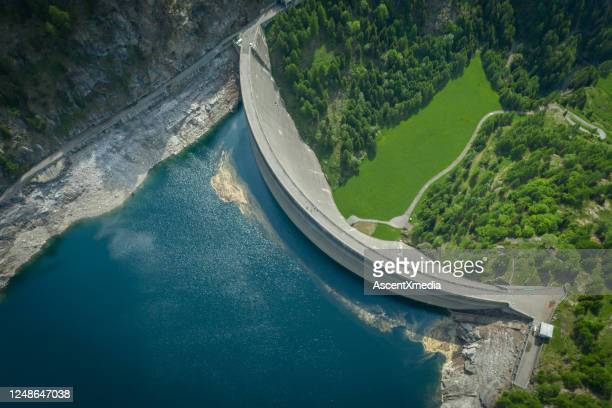 aerial view of bridge on large dam in swiss alps - reservoir stock pictures, royalty-free photos & images