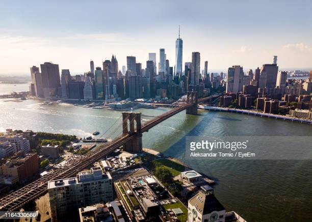 aerial view of brooklyn bridge over river in city against sky - brooklyn bridge stock pictures, royalty-free photos & images