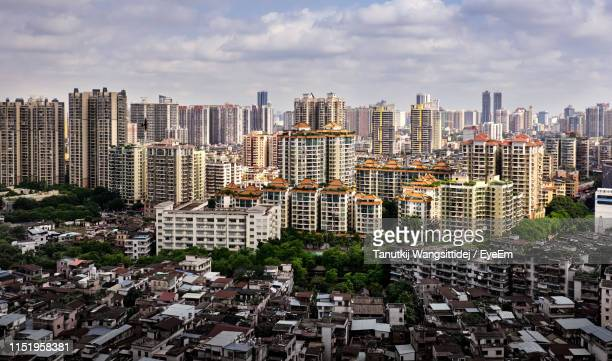 aerial view of buildings against cloudy sky in city - guangzhou stock pictures, royalty-free photos & images