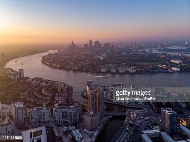 aerial view of buildings by river against sky in city during sunset - isle of dogs london stock pictures, royalty-free photos & images