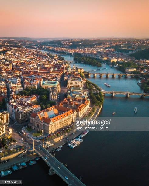 aerial view of buildings by river against sky - prague stock pictures, royalty-free photos & images