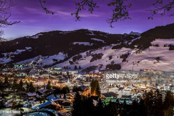 aerial view of buildings by snowcapped mountains against sky during winter - ムジェーヴ ストックフォトと画像