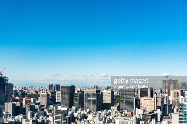 aerial view of buildings in city against clear blue sky - day ストックフォトと画像