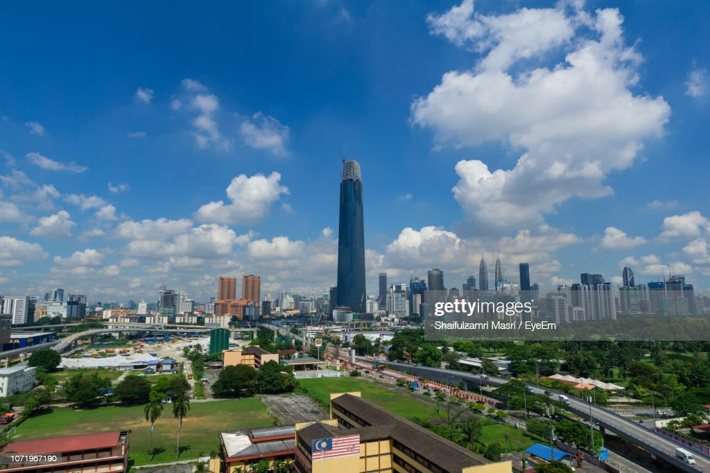 Aerial View Of Buildings In City Against Cloudy Sky : Stock Photo