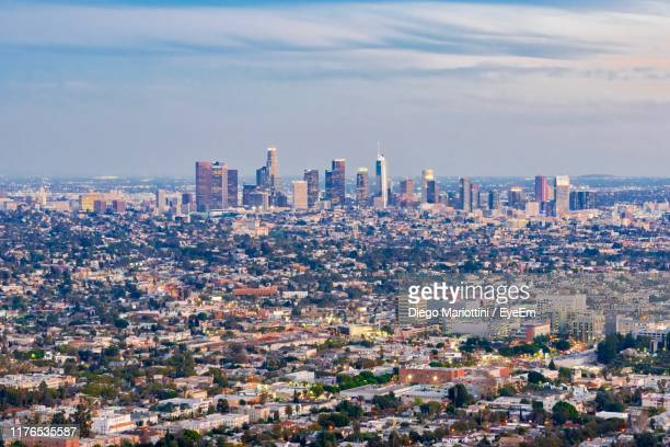 aerial view of buildings in city against cloudy sky - urban sprawl stock pictures, royalty-free photos & images