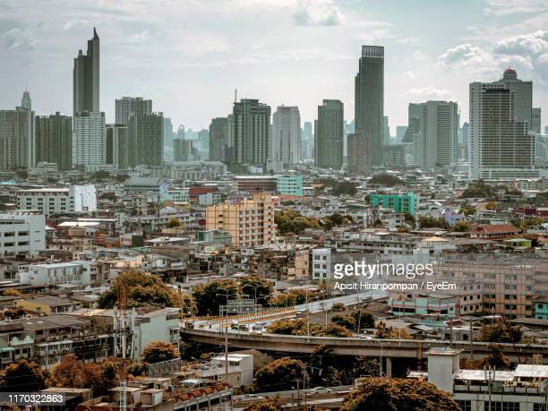 aerial view of buildings in city against sky - apisit hiranpornpan stock pictures, royalty-free photos & images