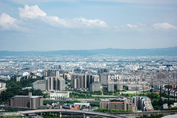 aerial view of buildings in city against sky - 吹田市 ストックフォトと画像