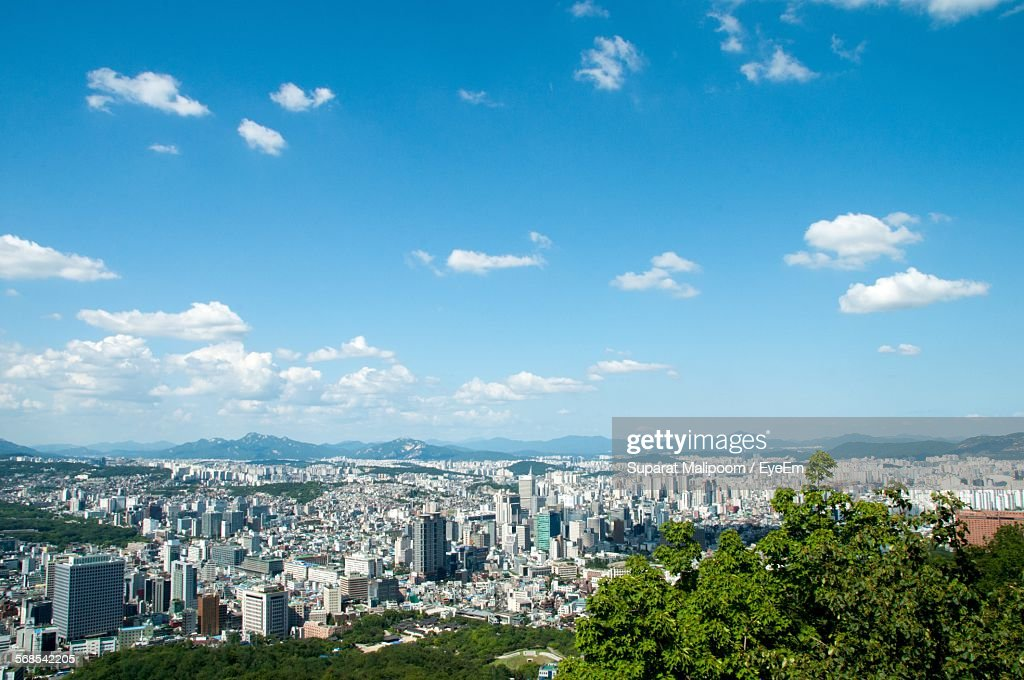 Aerial View Of Buildings In City In Front Of Mountains Against Cloudy Sky : Stock Photo