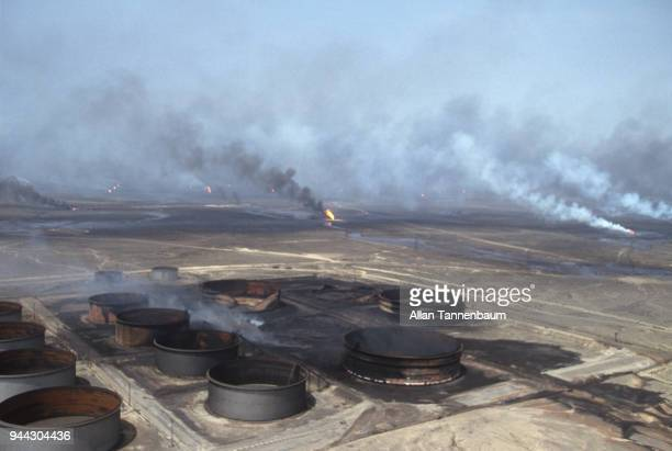 Aerial view of burntout oil storage tanks and burning wells Kuwait 1991