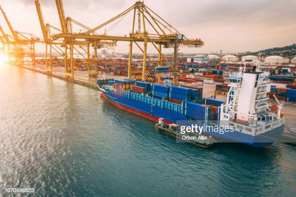 aerial view of business port with shore crane loading containers in freight ship. - commercial dock stock pictures, royalty-free photos & images