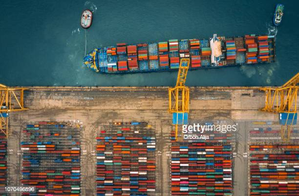 aerial view of business port with shore crane loading containers in freight ship. - shipyard stock pictures, royalty-free photos & images