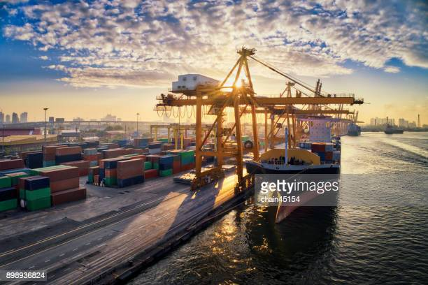 Aerial view of business port with Shore crane loading containers in freight ship. Container ship in import export and business logistics with crane and Shipping cargo. International transportation and Business logistics concept.