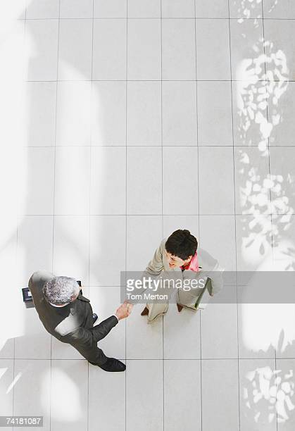 aerial view of businessman and businesswoman shaking hands - business relationship stock pictures, royalty-free photos & images