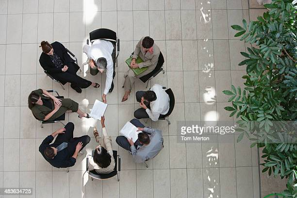 Aerial view of businesspeople sitting in circle with documents