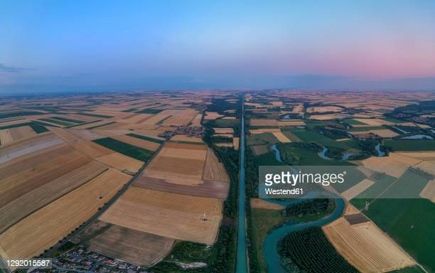 aerial view of canal lateral a la marne stretching between countryside fields at dusk - vista lateral stock pictures, royalty-free photos & images