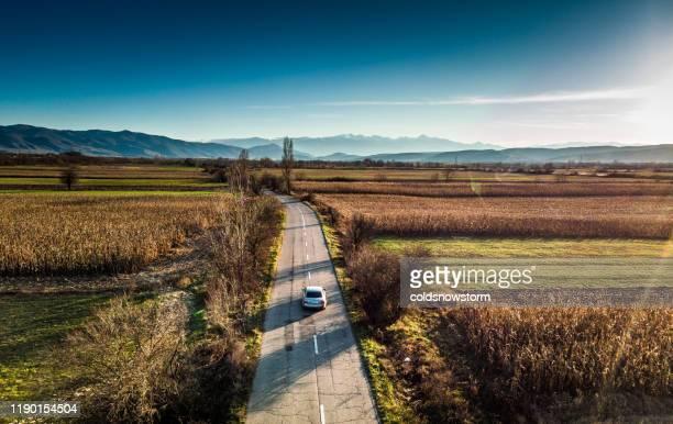 flygbild av bilkörning på raka landsväg genom landsbygdens vildmark - rumänien bildbanksfoton och bilder