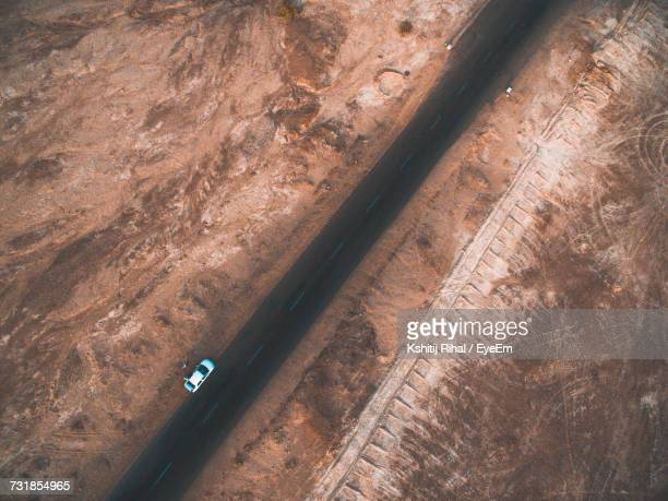 Aerial View Of Car Park On Road By Barren Landscape