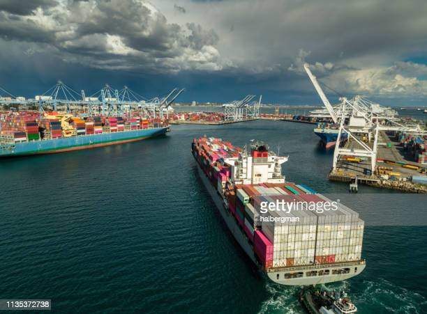 aerial view of cargo ship arriving in port - long beach california stock photos and pictures