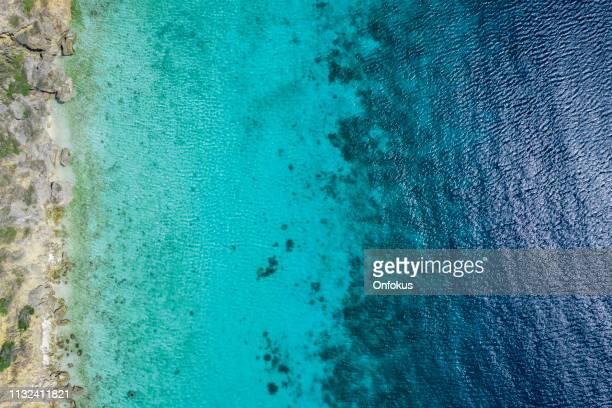 vue aérienne de la mer des caraïbes à curaçao - couleur corail photos et images de collection