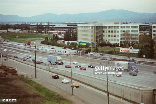 Aerial view of cars and trucks including a Matson Lines intermodal freight container at rush hour on the 580 freeway in Dublin California driving...