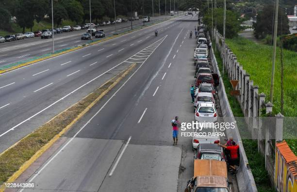 Aerial view of cars in line as drivers wait to refuel the tanks of their vehicles near a gas station in Caracas on September 10 amid the new...