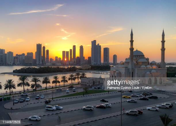 aerial view of cars on road by river against sky in city during sunset - mosque stock pictures, royalty-free photos & images