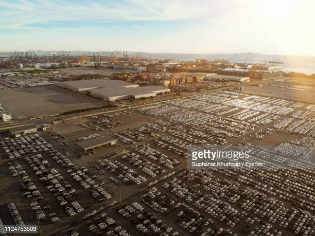 aerial view of cars parked by shipping yard against sky during sunset - abundance stock pictures, royalty-free photos & images
