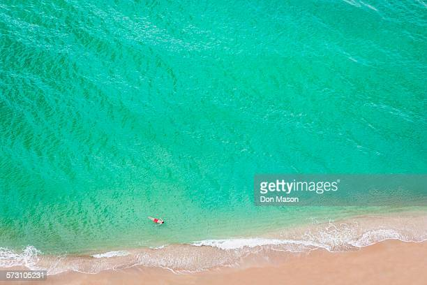 Aerial view of Caucasian man swimming in ocean on beach