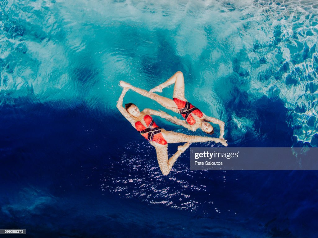 Aerial view of Caucasian synchronized swimmers : Stock Photo