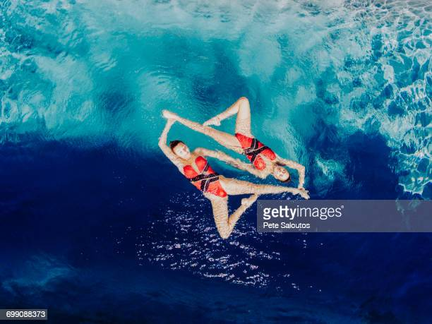 aerial view of caucasian synchronized swimmers - symmetry stock photos and pictures