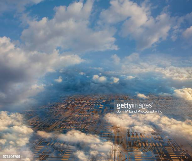 Aerial view of circuit board cityscape under clouds