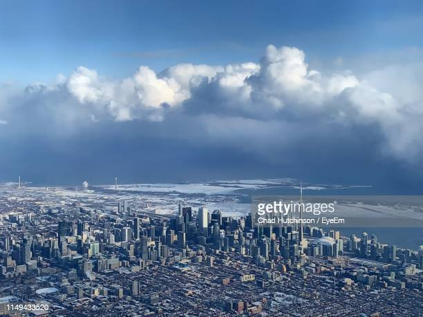 aerial view of city against cloudy sky - toronto stock pictures, royalty-free photos & images