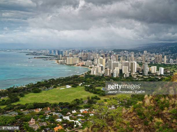 aerial view of city against cloudy sky - diamond head stock photos and pictures