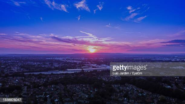 aerial view of city against sky during sunset - space and astronomy stock pictures, royalty-free photos & images