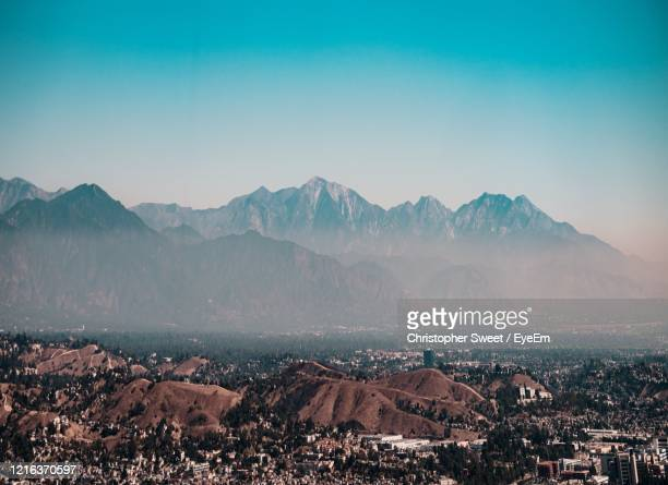 aerial view of city and mountains against clear sky - los angeles mountains stock pictures, royalty-free photos & images