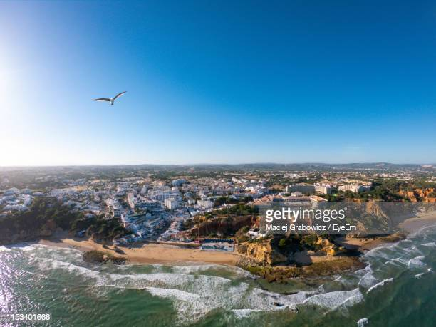 aerial view of city and sea against blue sky - albufeira stock pictures, royalty-free photos & images